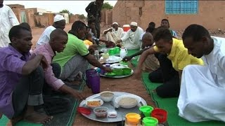 Residents of Khartoum break the fast on the first day of Ramadan by enjoying the traditional dish assida, a porridge-like lump served with stews, in the street with ...