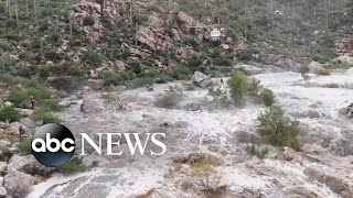 Two hikers remain trapped on a ledge above the fast-moving water of the Tanque Verde Falls as states from Kentucky to Delaware are also hit by severe weather.