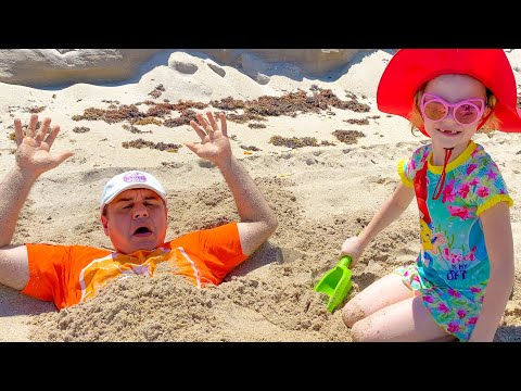 Nastya and dad play on the beach with toys