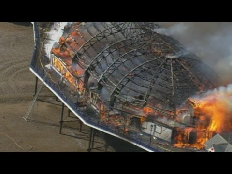 Footage - Subscribe here: http://bit.ly/1bmWO8h A huge fire has broken out at Eastbourne Pier after one of the arcade buildings caught alight at the popular seaside resort. At least 60 fire-fighters...