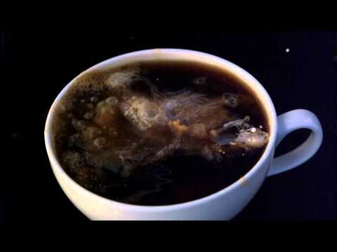 Pouring creamer into coffee in slow motion