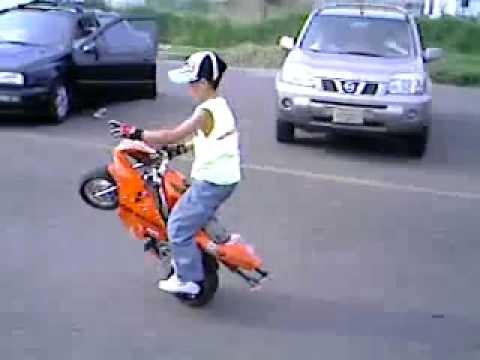 Un petit gère une mini moto