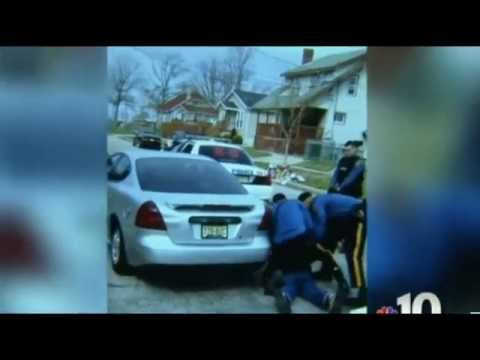 A police dog tears apart an unarmed black man's face while officers watch.