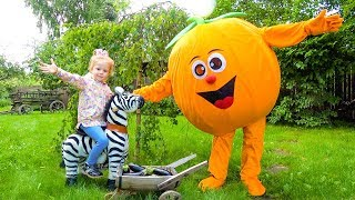Giant fruit toys and kid playing in the garden