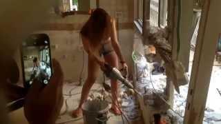 Красивая девушка на стройке с отбойным молотком ломает стены