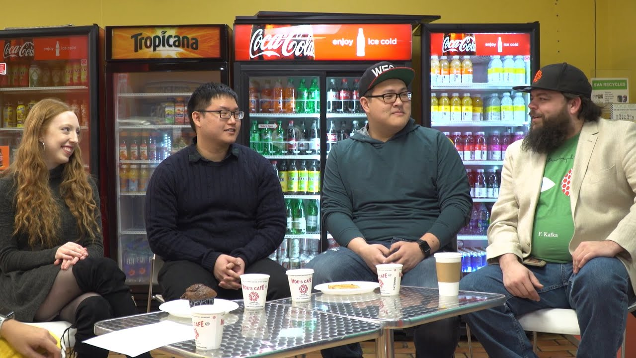 Four people speaking around a table next to some beverage dispensers.