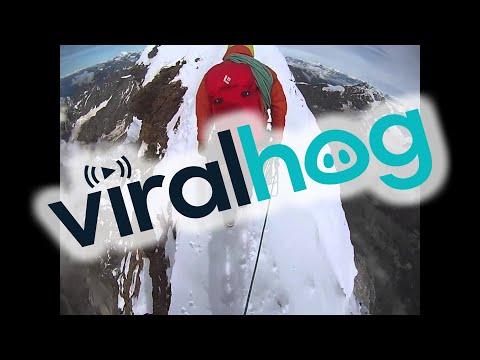 مغامر يسير على حد قمة أحد جبال الألب . مشهد مخيف .