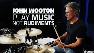 """World-renowned marching percussionist John Wooton is going to teach you how to use rudiments musically around the drum set. This includes learning several variations of commonly used rudiments, rudiments for articulation purposes, as well as how to use snare drum solos to help you hone in on your technique and musicality at the same time.LESSON INDEX:0:06 - """"Crazy Army"""" Snare Solo1:30 - Introduction3:35 - Play Music, Not Rudiments10:50 - Paradiddles14:21 - Musical Demo17:47 - Six Stroke Roll25:53 - Flam Tap & Inverted Flam Tap31:11 - Ratamacue & Paradiddle-diddle34:47 - Six, Nine, and Ten Stroke Rolls36:64 - Musical Demo41:41 - Sextuplet Six Stroke Roll46:30 - Swiss Army Triplets53:17 - Question from Pat Petrillo57:51 - Snare Drum EtudeTry Drumeo Today!►http://www.Drumeo.com/trial/Follow us!►Facebook: http://www.facebook.com/Drumeo/►Instagram: http://www.instagram.com/Drumeoofficial/Download the sheet music:►http://www.Drumeo.com/blog/john-wooton-snare-drum-lessons/John plays:Pearl DrumsSabian CymbalsVic Firth Sticks"""