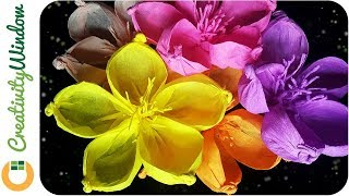 Grab your crepe papers, gold ball of other kinds of balls of similar size, barbecue sticks, scissors and adhesive tape; let us make a colorful rounded-petal crepe paper flower.