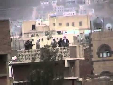 Saleh's security thugs (snipers) shoot at peaceful protesters from a roof