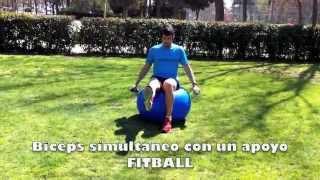 Biceps simultaneo sentado sobre fitball con mancuernas en un apoyo