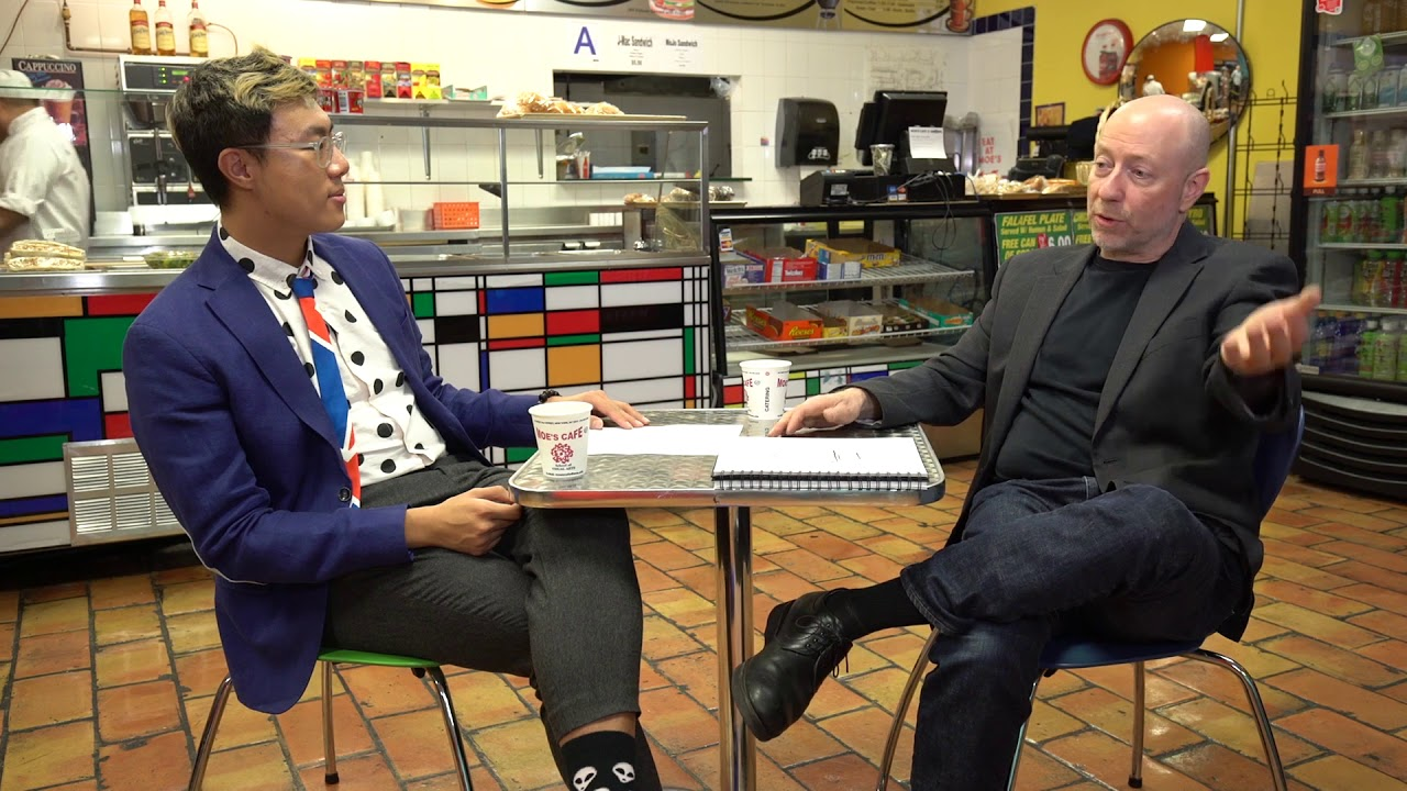 A man in a colorful suit speaking to a older man.