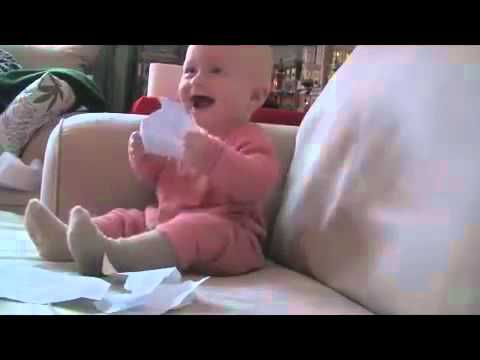 Lustiges Baby lacht wegen Papier
