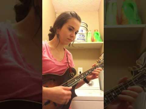 Nainen soittaa kitaraa ja pesukone toimii rumpalina