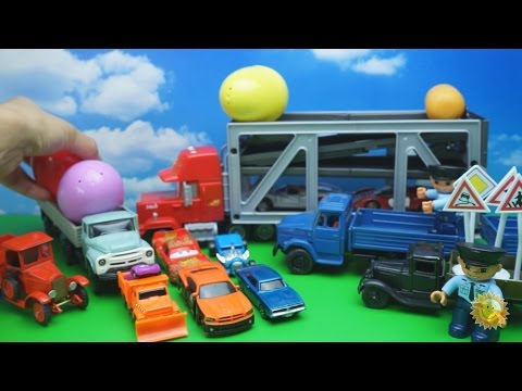 Überraschung mit Spielautos. Überraschungseier. Transportwagen Mack und LKWs. Spielautos für Kinder