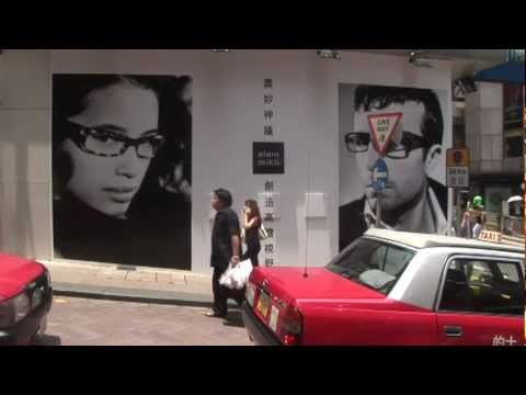 Hong Kong HK Red Taxis passing an Advertisement for Alain Mikli Designer Glasses i… видео
