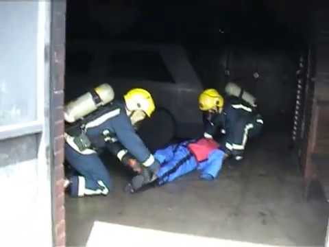mannequin-man performming as a drag dummy: Video clip of a fire drill drag dummy being carried out of a firehouse by two trainee fire recruits during Breathing Apparatus training at West Midlands Brigade Training Centre for West Mids Fire Service on 24/05/2003