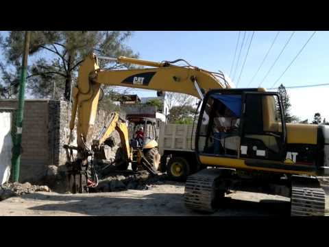 retro excavadora - La retroexcavadora y excavadora trabajando en equipo para librar un camino rocoso. La excavadora trabaja con un martillo, un martillo hidráulico con el que t...