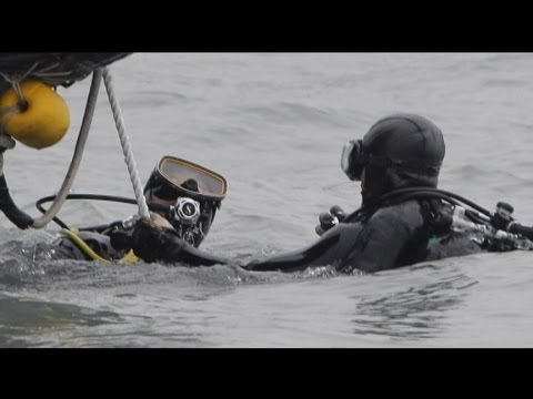 Off - Underwater video of divers struggling to reach ship's cafeteria where it's believed many were trapped.