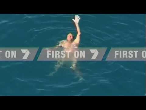 Uomo in mezzo al mare circondato da squali