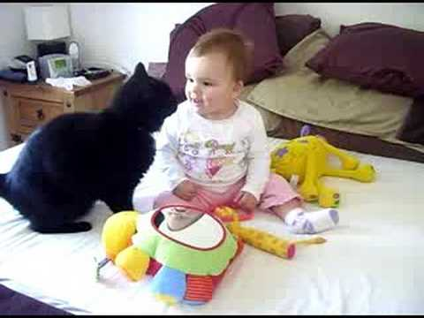 「[ネコ]赤ちゃんのほっぺに尻尾をさすり、赤ちゃんを大喜びさせる猫。」のイメージ