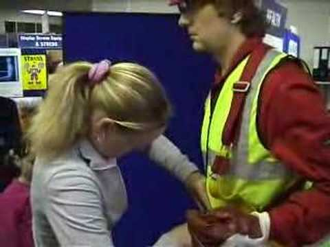 mannequin-man performming as a Living Mannequin: Fall arrest harness being put onto mannequin man by member of the public at a Safety clothing and PPE exhibition by ARCO at family open day at BAE (British Aerospace Engineering) systems in Rochester #3 (flash) for Arco on 06/07/2002