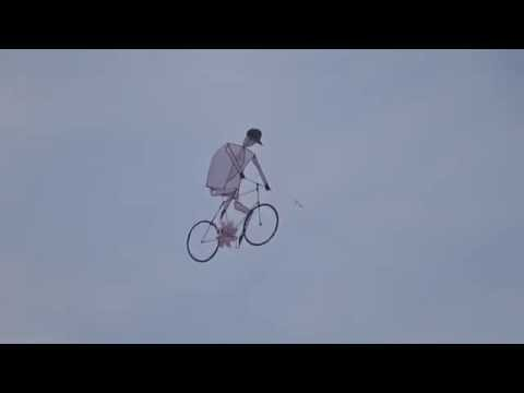 Is that a Kite, or a guy riding a bike?