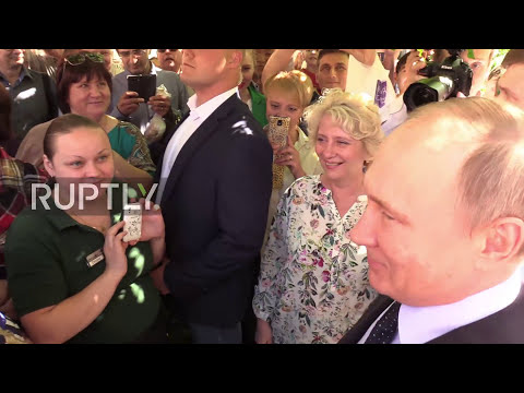 Russia: Cheeky much? Female tourist steals a kiss from Putin