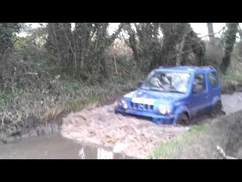 Group of Suzuki Jimny offroad 4x4's driving the Water Lane greenlane water splash offroad