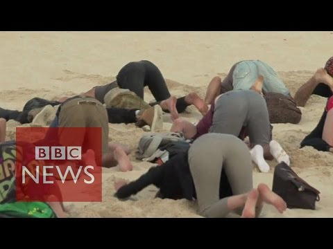 Climate protesters bury heads in sand