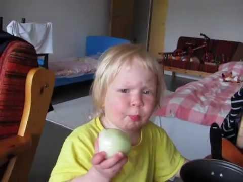 Cute kid eats a raw onion like an apple