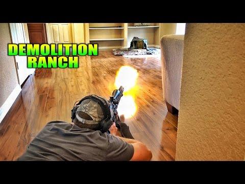 Mies testailee aseitaan omassa olohuoneessa