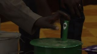 Gambia's Independent Electoral Commission demonstrates the country's unique way of choosing their president, with voters dropping marbles into coloured metal...