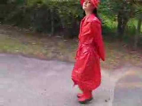Rainweargirl - Walking in a red PVC raincoat from PVC-U-Like. I also wear a matching rainhat & camisole and purple PVC jeans. The red rubber boots are from Sweden.