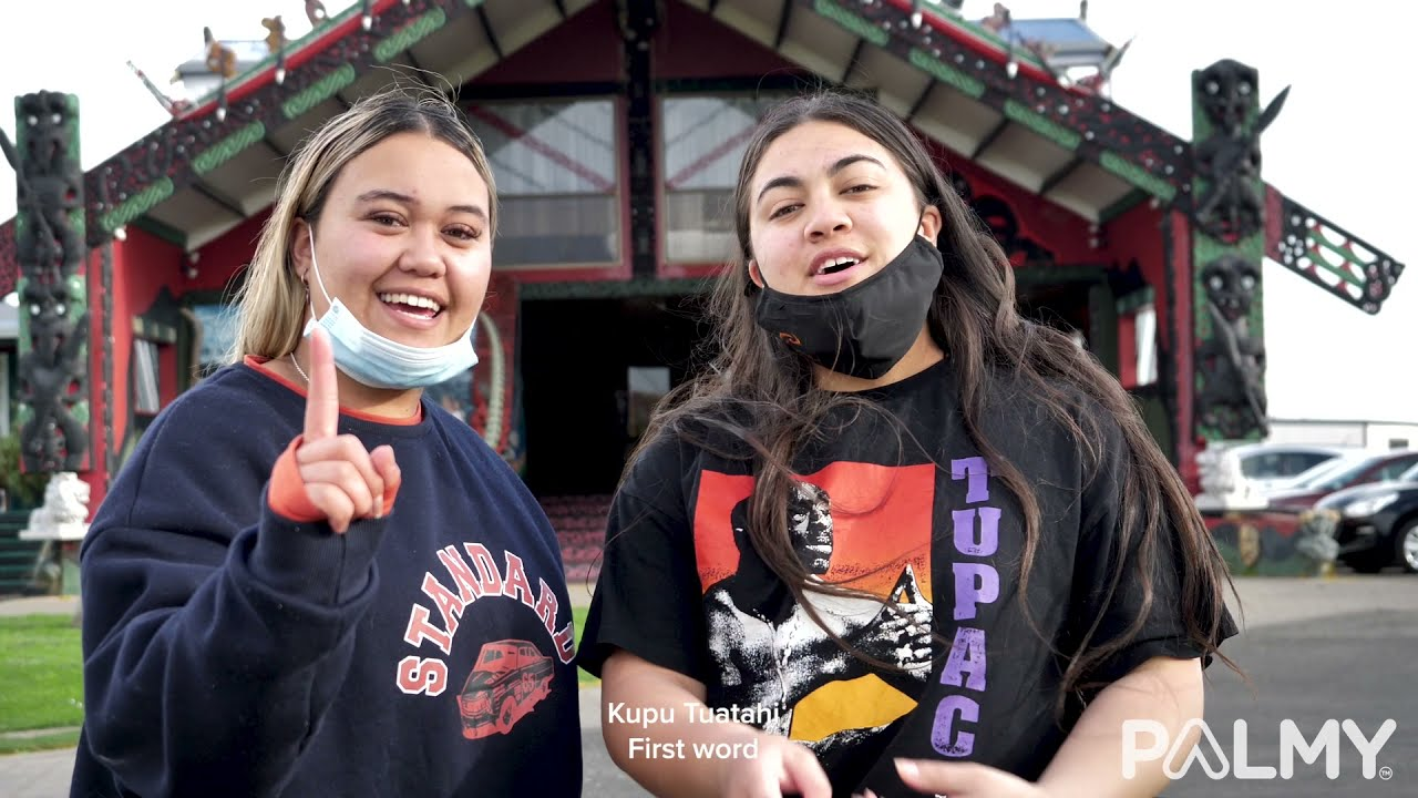YouTube placeholder image shows two young women wearing masks outside the marae.