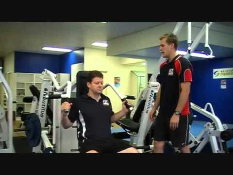FITCollege - http://www.FitCollege.edu.au/ Today our Fit College Trainer Mark, shows Matt how to use the Vertical Shoulder Press Exercise Machine. Discover what muscles t...