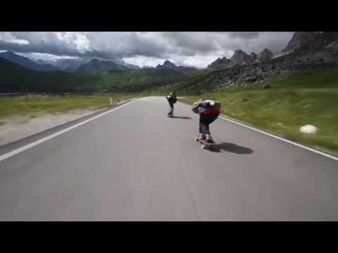 three skateboarders passing cyclists as they descend the alps