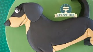 How to make a sausage dog cake, specifically a Dachshund cake! This is more of a beginner cake decorating tutorial so anyone can make this! :)Tools and products used in this video - Dachshund template - https://tinyurl.com/luxw6rrRenshaw's fondant Black - http://amzn.to/2lXT7BmCake modelling tool - https://www.facebook.com/commerce/products/1878762348816211/Craft mat - http://amzn.to/2dMKpl9 Teddy bear brown fondant - http://amzn.to/2oKZr0ABasic Victoria sponge cake recipe - Ingredients: 225g butter225g caster sugar4 eggs225g self-raising flour 1 tsp vanilla essenceMethod:Cream together the butter and sugar, then beat in the eggs and vanilla essence. Once smooth and creamy, fold in the flour.Pour in to a greased cake tin and bake in the oven at 180degrees for approximately 40 minutes, until golden brown and a knife comes out clean.Buttercream recipe - 600g icing sugar, sifted300g unsalted or salted butter, softenedoptional flavouringBeat the ingredients together.To see more of my cakes and creations please visit my pages below-Facebook https://www.facebook.com/zoesfancycakes Twitter https://twitter.com/zoesfancycakesInstagram https://instagram.com/zoesfancycakes/Website http://www.zoesfancycakes.co.uk/You can also check out my online courses with 25% off below! :)Faces - https://www.udemy.com/how-to-make-sugar-craft-faces/?couponCode=YT25OFFRoses - https://www.udemy.com/how-to-make-sugar-craft-roses/?couponCode=YT25OFF