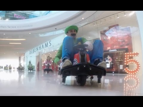 EJ: Watch These Two Friends Dress Up And Play Mario Kart In The Mall.