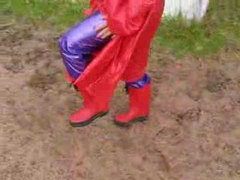 Rainweargirl - Second part of me walking in red PVC coat, camisole, rainhat, boots and purple PVC jeans.