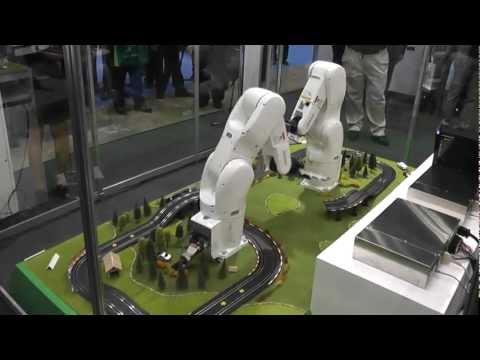 The two DENSO VS068 robots are laying a slot car track for Super Mario's drive!