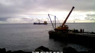 Unloading a cargo ship with general supplies. Cascade Bay jetty, Norfolk Island Australia. Time lapse video 2 frames per second.