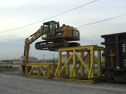 rail - Caterpillar 319D LN climbing onto a rail car to unload crushed rock in Kansas City.
