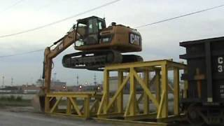 Caterpillar 319D LN climbing onto a rail car to unload crushed rock in Kansas City.