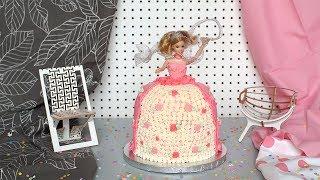 """Una muñeca Barbie se viste de fiesta de cumpleaños con un """"vestido"""" de pastel de vainilla decorado con betún de mantequilla. Encuentra la receta completa en Allrecipes México: http://allrecipes.com.mx/receta/12355/pastel-de-princesa-para-cumpleanos.aspx"""