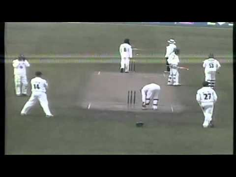Murali bowling with an arm brace