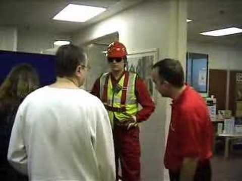 mannequin-man performming as a Living Mannequin: Fall arrest harness being put onto mannequin man by member of the public at a Safety clothing and PPE exhibition by ARCO at family open day at BAE (British Aerospace Engineering) systems in Rochester #7 (flash) for Arco on 06/07/2002