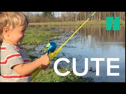 This kid catches a fish with his toy fishing rod while his dad encourages him