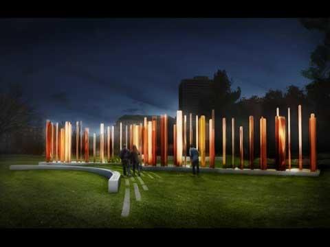 Des visiteurs s'approchent des hautes colonnes élancées, de couleur bronze, qui sont illuminées en soirée.