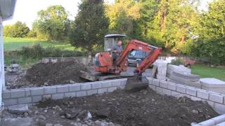 Mini-excavator digs through a driveway to prepare for the building of an extension. Also included is the pouring of ready mix concrete.